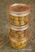 Three jars of home canned olives in the kitchen