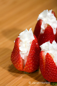 Sliced strawberries filled with whipping cream on a wood cutting board
