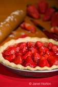 Whole strawberry pie with rolling pin dusted with flour, knife, and whole and sliced strawberries in the background