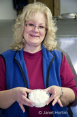 Woman (Cindy) holding a plastic bowl of feta cheese during a cheesemaking class at River Valley Farm
