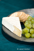 Smoked Baby Brie, water crackers and yellow grapes on plate