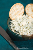 Bowl of crumbled blue cheese with water crackers and knife