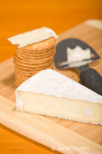 Smoked Baby Brie cheese, cheese slicer and whole wheat water crackers on cutting board
