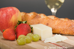 Gruyere Swiss cheese, fruit, glass of wine and cheese bread on cutting board