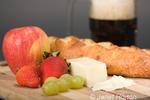 Gruyere Swiss cheese, mug of beer, fruit and cheese bread on cutting board