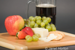 Gruyere Swiss cheese, mug of beer, fruit and whole wheat water crackers on a cutting board