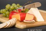 Gouda cheese, Beecher's Flagship cheese, knife, water crackers and grapes on cutting board
