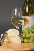 Smoked Baby Brie, grapes, water crackers, knife, glass and bottle of wine on cutting board