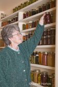 Woman in pantry of preserved fruits and vegetables in canning jars