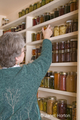 Woman in full pantry of preserved fruits and vegetables in canning jars