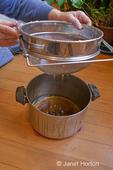 Straining raw knotweed (Japanese) honey into a pot sitting on a hardwood floor