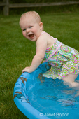 One year old, Ella, playing in a wading pool