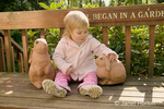 "Joanna (1.5 years old) sitting on a garden bench that says ""It all began in a garden"" fondly petting the rabbit statues"