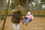 Grandmother pushing two year old granddaughter in a swing, who is giggling and enjoying it thoroughly