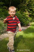 Two year old boy, Joshua, running with a small ball in his hand in the backyard