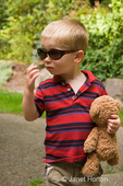 Two year old boy, Joshua, carrying a teddy bear and wearing askew Mom's sunglasses, looking like he wants to disguise himself from the paparazzi