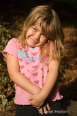 Four year old girl, Joanna, shrugging her shoulders and looking very cute, with a 