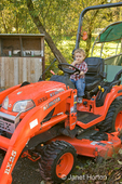 Toddler boy sitting on BX25 tractor pretending to drive it at Baxter Barn