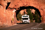 Truck driving through tunnel on unbanked curve in highway