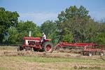 Man on International Harvester Farmall tractor, raking hay in a field