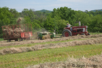 Man on International Harvester Farmall tractor, baling hay in a field with a bale flying in the air
