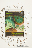 Organic broccoli seed packet with seeds beside it.