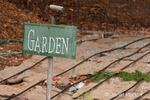 Garden sign and burlap bags covering vegetable garden to mulch, protect from weeds and winterize, showing drip irrigation tubes, at a community pea patch garden