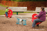Ethnic boy & mother playing on teeter totter at the playground