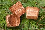Three handmade Western Red Cedar baskets woven from strips of inner bark, lying on Western Red Cedar branches