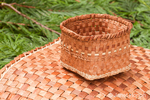 Hand-woven mat and basket made from the pliant inner bark of a Western Red Cedar tree, resting on Western Red Cedar branchlets in Western Washington