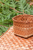 Hand-woven mat and basket made from the pliant inner bark of a Western Red Cedar tree, resting on Western Red Cedar branchlets