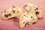 Three home made cranberry, lemon and almond scones on a red and white checkered cloth