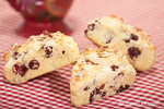 Three home made cranberry, lemon and almond scones on a red and white checkered cloth with a red mug in the background