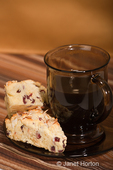 Home made cranberry, lemon and almond scones on a plate with a mug of coffee on a brown striped tea towel