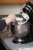 Woman, Kath, adding yeast into bowl of KitchenAid mixer, as part of making bread
