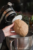 Woman, Kath, about to take bread dough off of bread hook on KitchenAid mixer