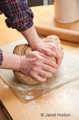Woman, Kath, kneading a multi-loaf multigrain bread dough