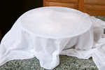 Damp cloth covering a large mixing bowl of bread dough rising on a granite counter