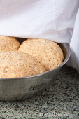 Three balls of multigrain bread dough that have risen sufficiently, being uncovered of damp cloth