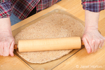 Woman, Kath, rolling ball of bread dough with a rolling pin to flatten it, prior to forming it into a loaf