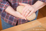 Woman, Kath, shaping multigrain bread dough to form a loaf, which has not first been rolled