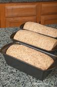 Three bread pans of multigrain dough ready for final rising
