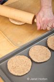 Woman, Kath, rolling multigrain bread dough into circles to make hamburger buns