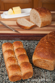 Multigrain rolls and loaf with a slice cut off, with butter and a bread knife