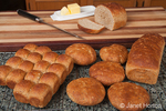 Multigrain rolls, buns and loaf with a slice cut off, with butter and a bread knife