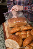 Woman, Kath, placing a loaf of multigrain bread into a plastic bag to store it
