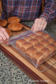 Woman, Kath, placing multigrain bread rolls into a plastic bag to store them