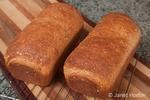 Multigrain bread loaves on a cooling rack on a bread board