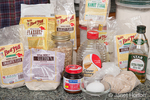 Breadmaking ingredients (various flours, honey, oats, yeast, egg, olive oil, flaxseed, etc.)