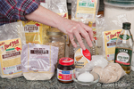 Woman, Kath, reaching for honey in a grouping of breadmaking ingredients (various flours, honey, oats, yeast, egg, olive oil, flaxseed, etc.)